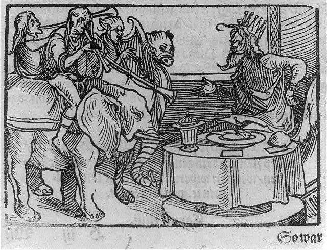 A bearded man, wearing a crown, seated at table facing several others with long horns, harp(?), and an elephant