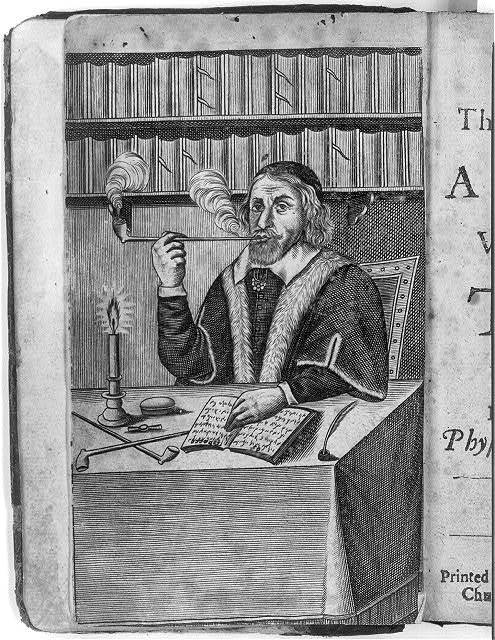 Man smoking a long pipe, seated at table with book, candle and 2 more long pipes