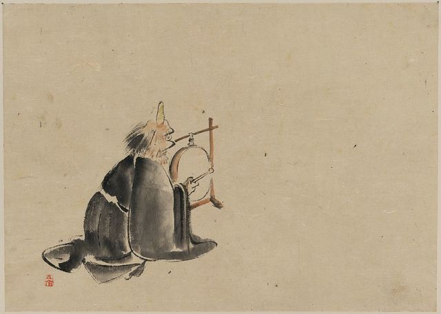 [A monk wearing a mask(?) with a horn, sitting on the ground, beating a drum (tsuri-daiko)]