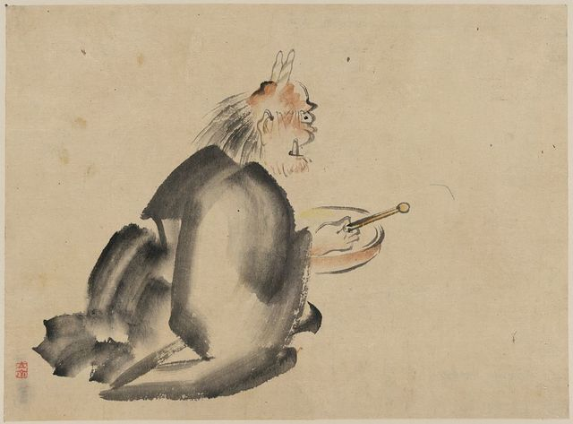 [A monk wearing mask(?) with horns, sitting on the ground, beating a drum]