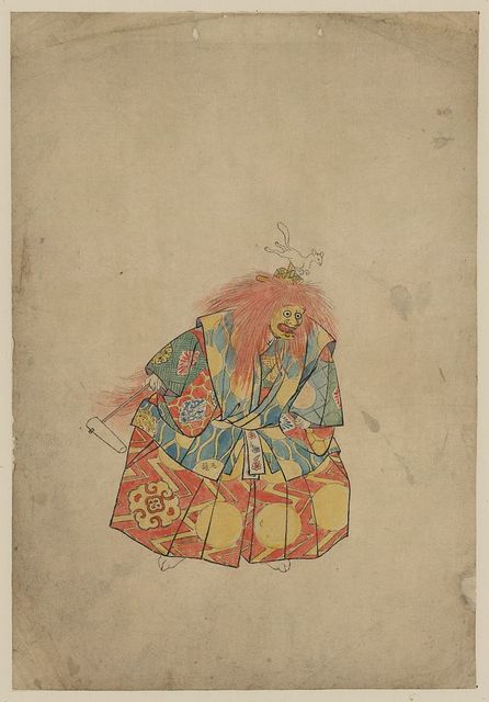 [A clown wearing colorful costume and mask, with wild hair and hat with animal on top, and holding a rattle]