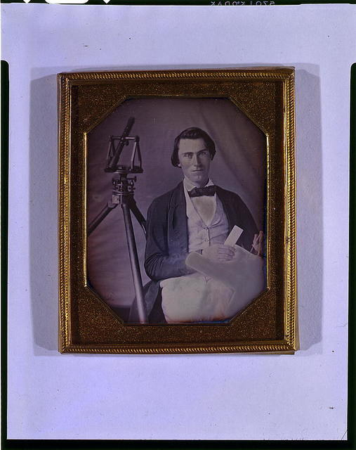 [Occupational portrait of an unidentified surveyor with a transit on a tripod and holding dividers and a map, three-quarter length, seated]