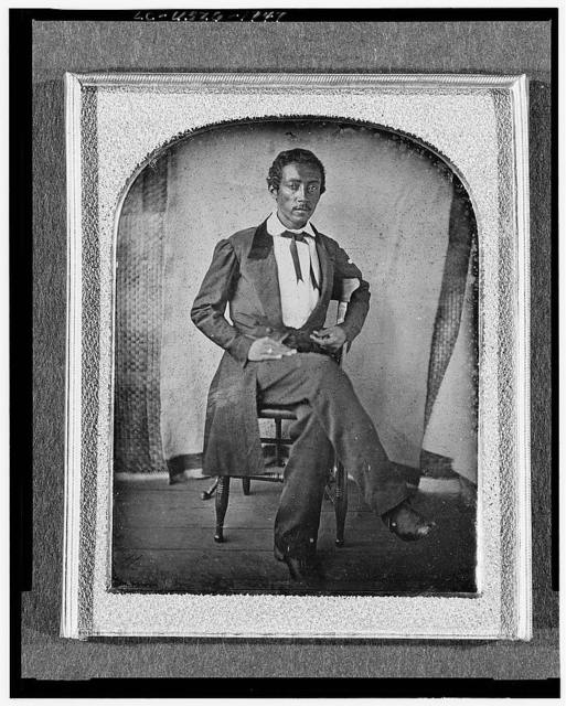 [R. McGill, full-length portrait, seated in chair, facing front, with textile screen in background]