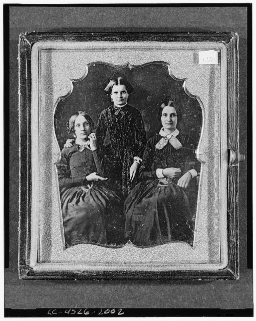 [Three unidentified women, two seated, one standing, facing front]