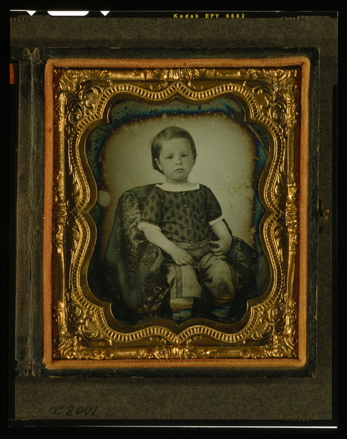 [Unidentified boy, three-quarter length portrait, seated in chair covered with drapery]