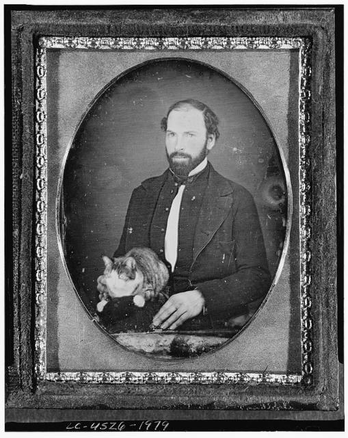 [Unidentified man with cat, three-quarter length portrait, full face, seated]
