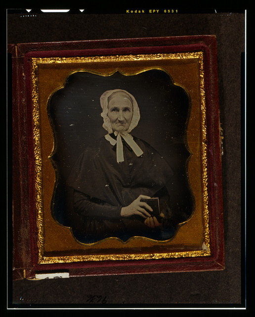 [Unidentified woman, head-and-shoulders portrait, facing front, wearing white cap and holding daguerreotype case]