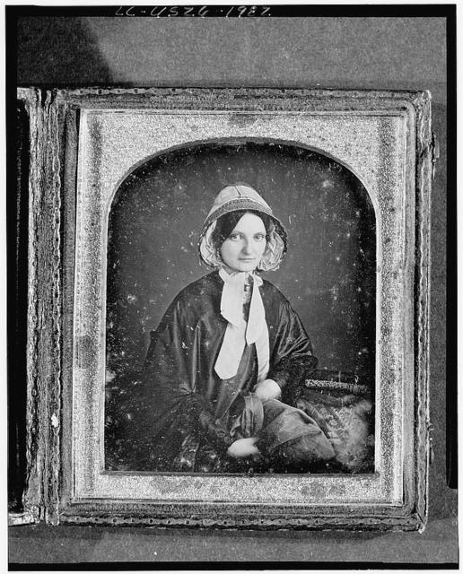 [Unidentified woman, three-quarter length portrait, facing front, with bonnet, arm resting on table with tablecloth; books on table]