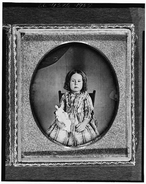 [Unidentified girl, three-quarter length portrait, facing front, seated in chair, holding doll]