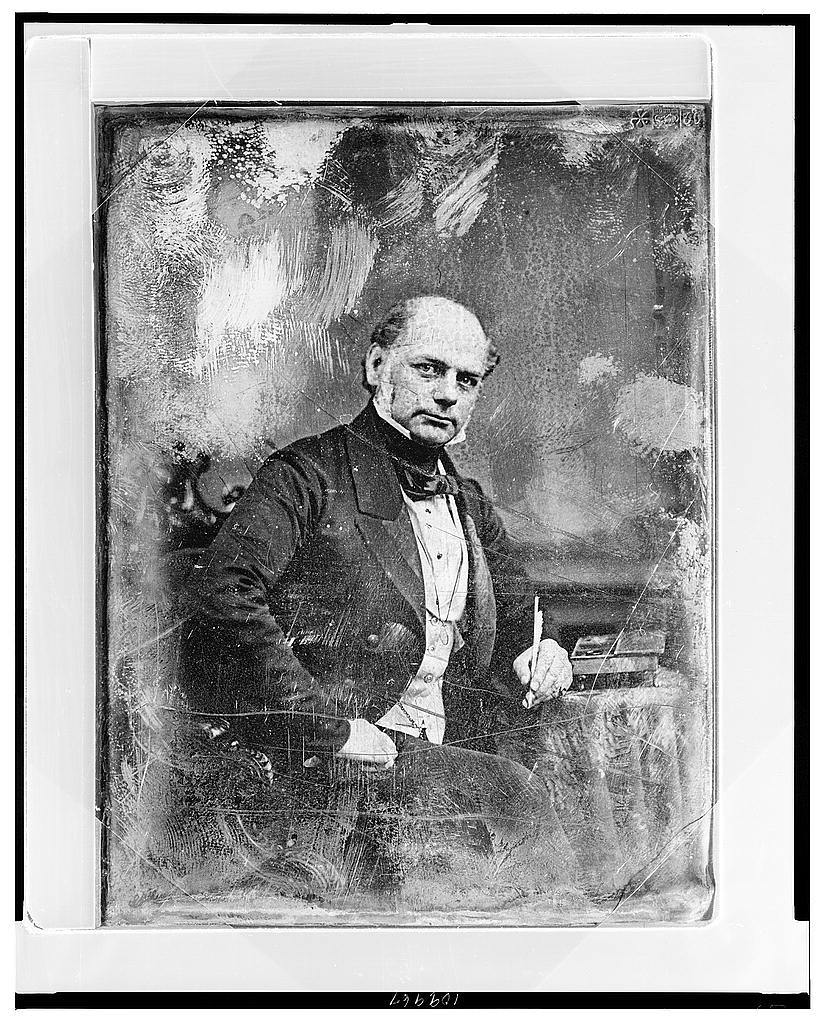 [Forbes Winslow, three-quarter length portrait, three-quarters to the right, eyes front, seated in chair at table with escritoire, holding quill pen]