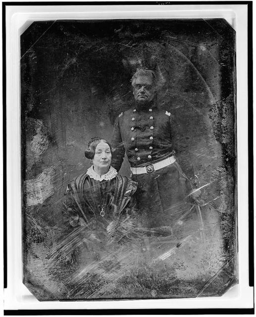 [Military officer and a woman, the officer in uniform, standing, facing front, the woman seated, on the left, nearly full face]
