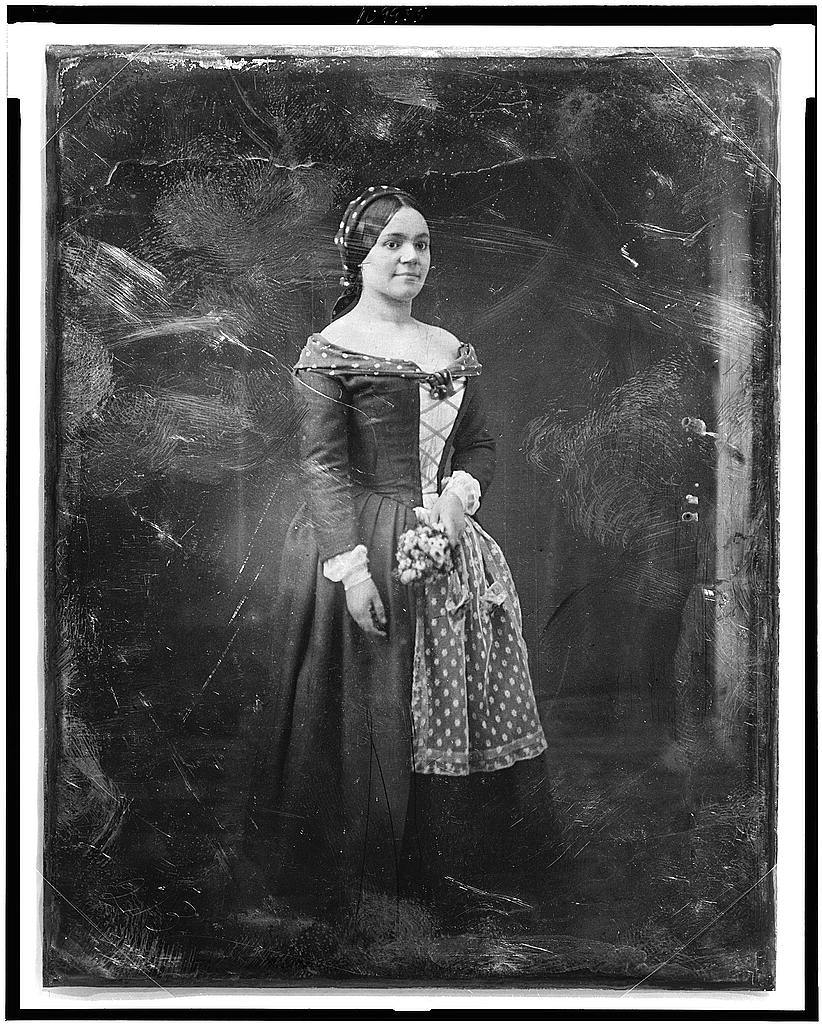 [Rosalie Henriette Bediez Laborde, full-length portrait of a woman, three-quarters to right, standing, in costume with lace apron, holding bouquet]