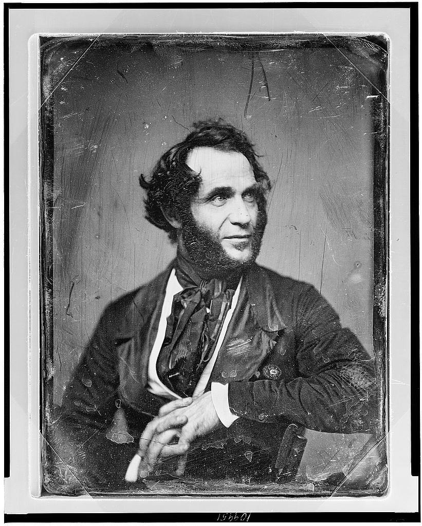 [Unidentified man, about 40 years of age, half-length portrait, slightly to left, head three-quarters to right, arm over back of chair, hands clasped in front, with heavy side whiskers]