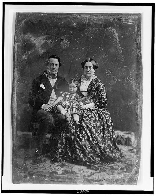 [Unidentified man and woman, both about 30 years of age, with a child about two years of age seated on woman's knee, full-length portraits, facing front, seated on chairs on carpet]