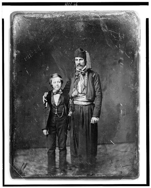 [Unidentified man in Middle Eastern costume with arm around boy, full-length portrait]