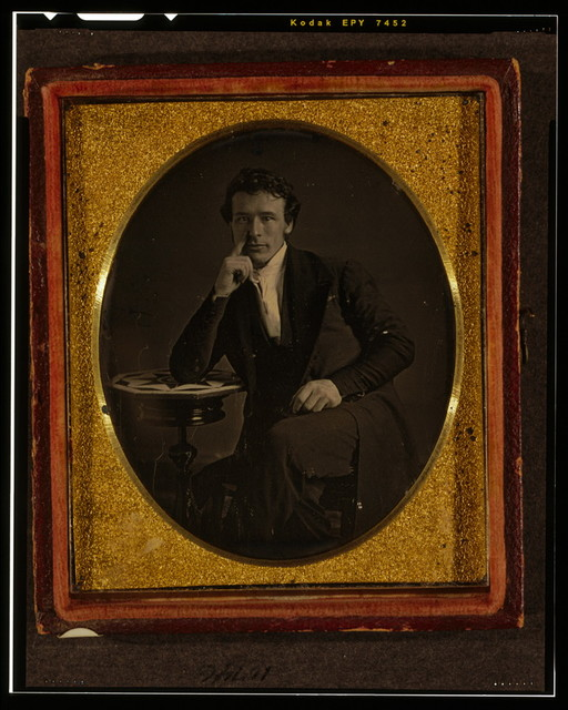 [Unidentified man, possibly John Jabez Edwin Mayall, three-quarters length portrait, seated, with right elbow resting on table]