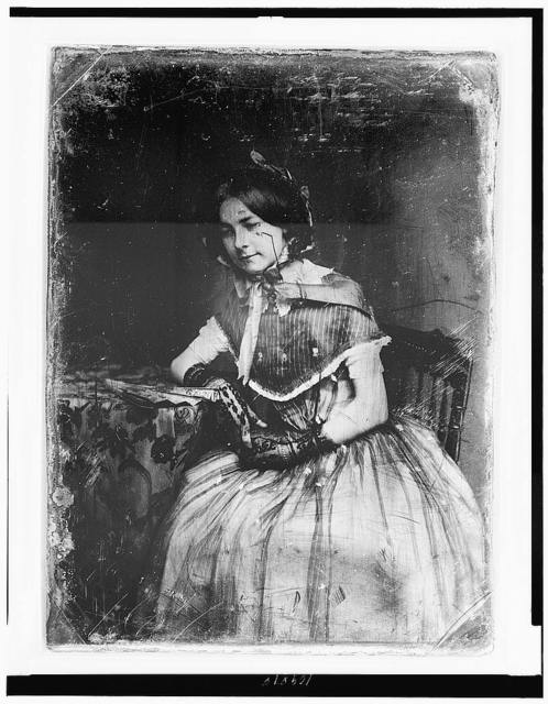 [Unidentified woman, about 20 years of age, three-quarter length portrait, three-quarters to the left, seated in chair beside small table with tablecloth, wearing bonnet and black lace gloves; hands in lap, one elbow on table on which there is a folded fan]