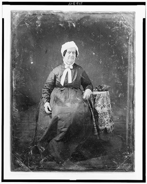 [Unidentified woman, about 60 years of age, full-length portrait, facing front, seated beside small table with tablecloth and handbag, wearing white cap]