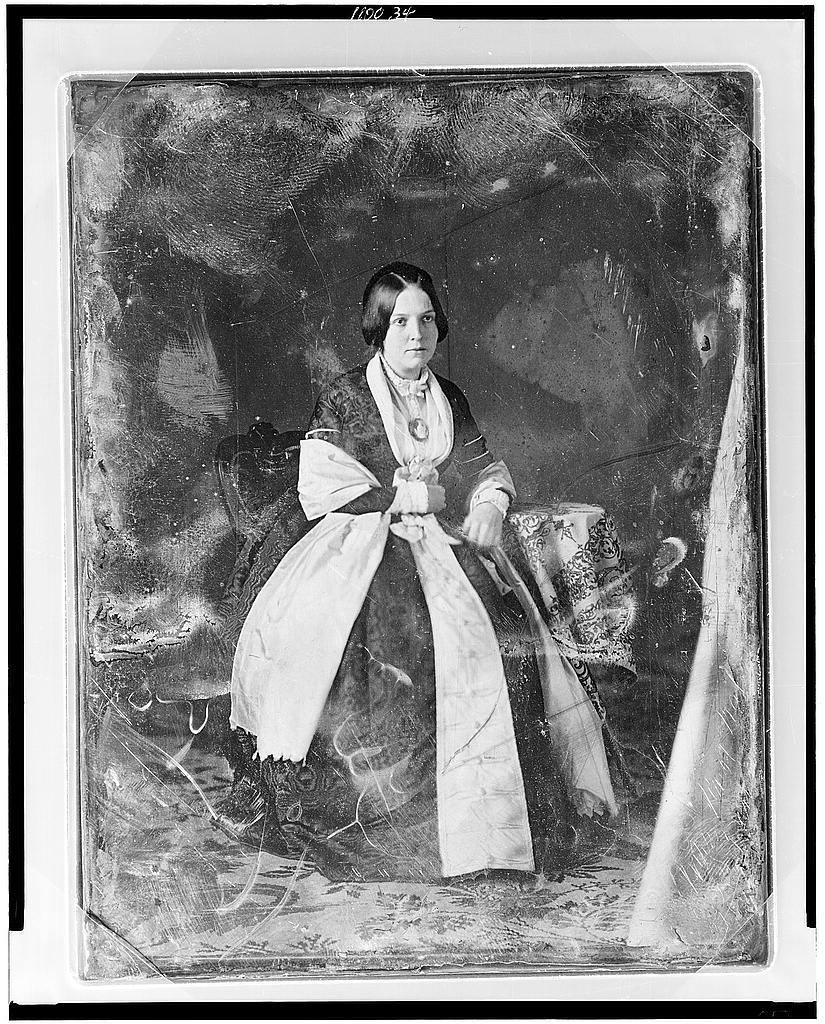 [Unidentified woman, full-length portrait, three-quarter to the right, seated in chair at a small table with tablecloth]