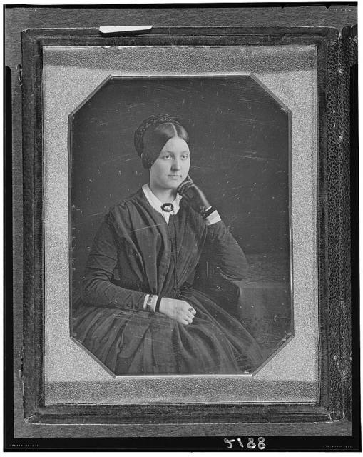 [Anna R.L. Baker, three-quarter length portrait, seated, with arm on table, wearing glove on one hand]