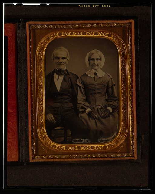[Unidentified man and woman, three-quarters length portrait, seated]