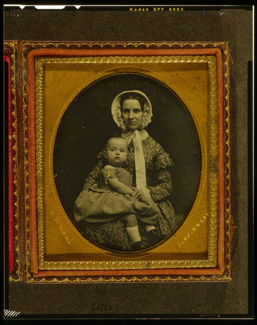 [Unidentified woman holding child in her lap]