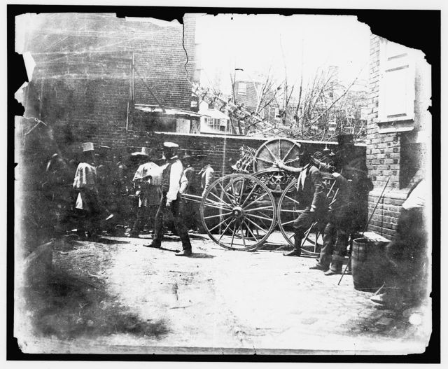 [Men pulling Reliance Fire Company hose carriage]