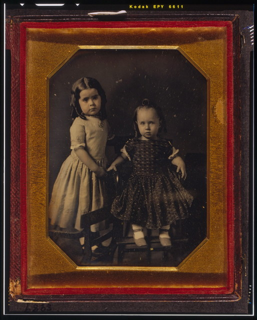 [Elisa and John McAllister, children of W.Y. McAllister, Elisa standing on chair, John sitting in high chair]