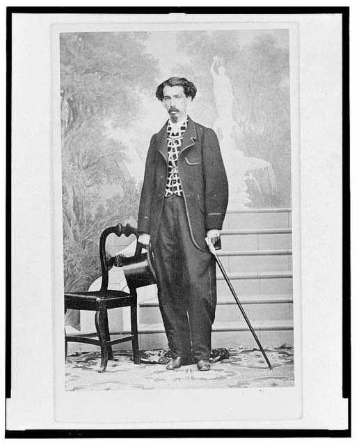 [Full-length portrait of a man holding top hat and cane, standing beside chair, facing front, stairs and mural in background]