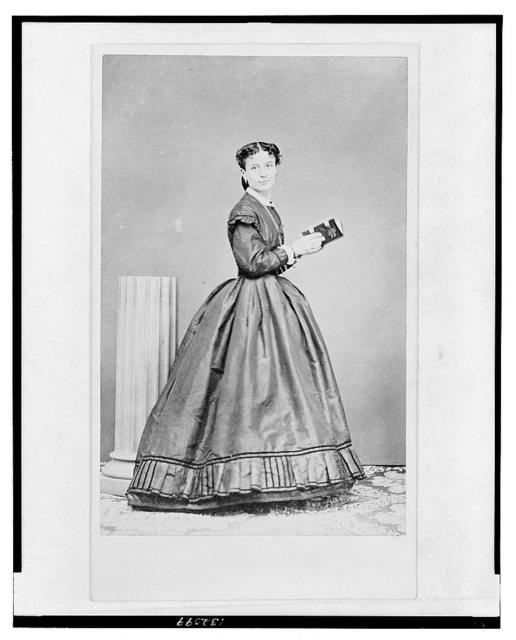 [Full-length portrait of a woman, standing, turned right, facing front, holding a book]
