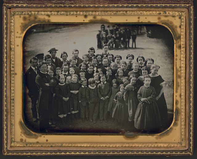 [Large group of school children, with their teacher, standing in a town street]