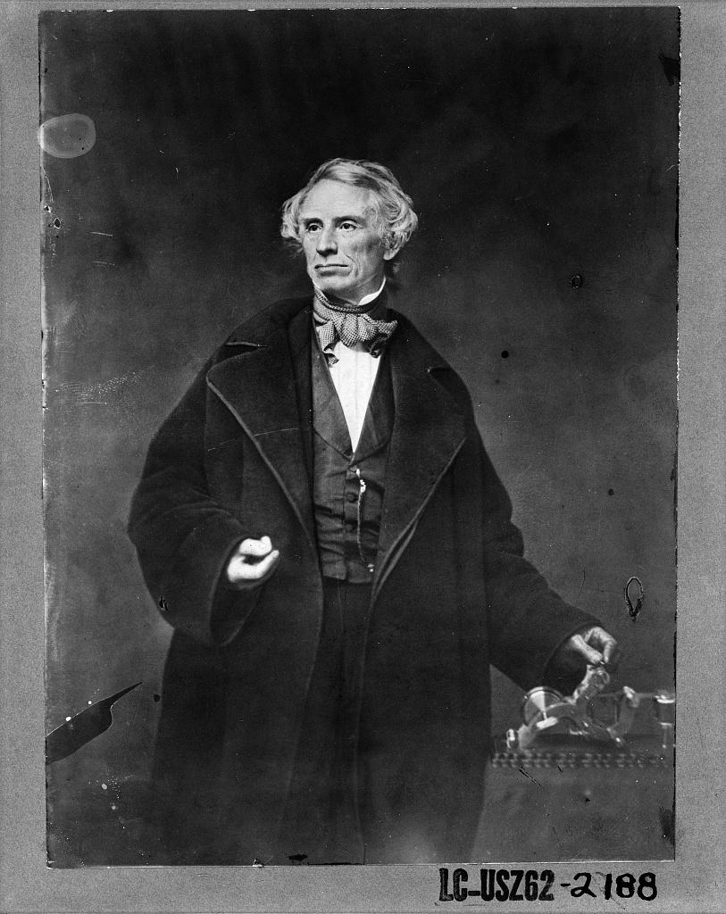 [Samuel F.B. Morse, half-length portrait, posing with left hand on a telegraph apparatus, facing slightly left]