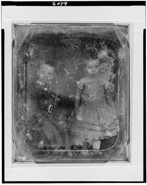 [Two unidentified children, a boy and girl, full-length portraits, seated]