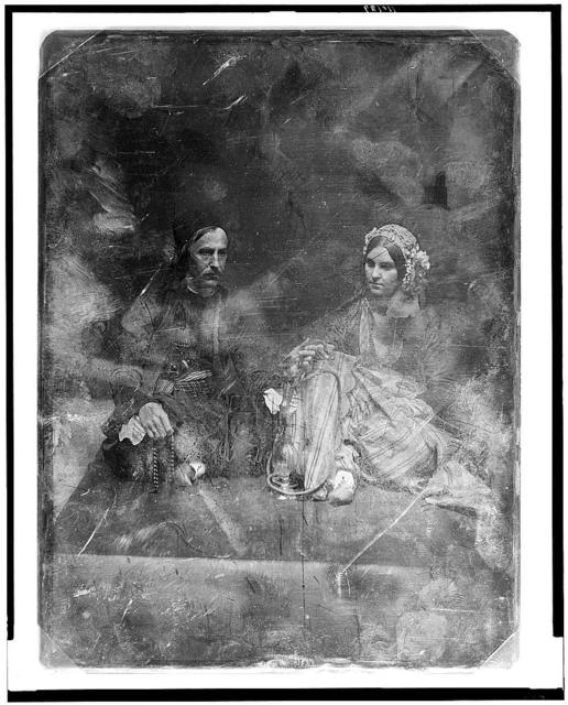 [Unidentified man, about 40 years of age and a somewhat younger woman, both in Oriental costume, full-length portraits, both seated on a carpet on the floor, the man, on the left, cross-legged, turned three-quarters to the right, holding a string of beads; the woman turned slightly to the left, wearing a beaded (?) cap; between them is a hookah, the stem of which both are holding]