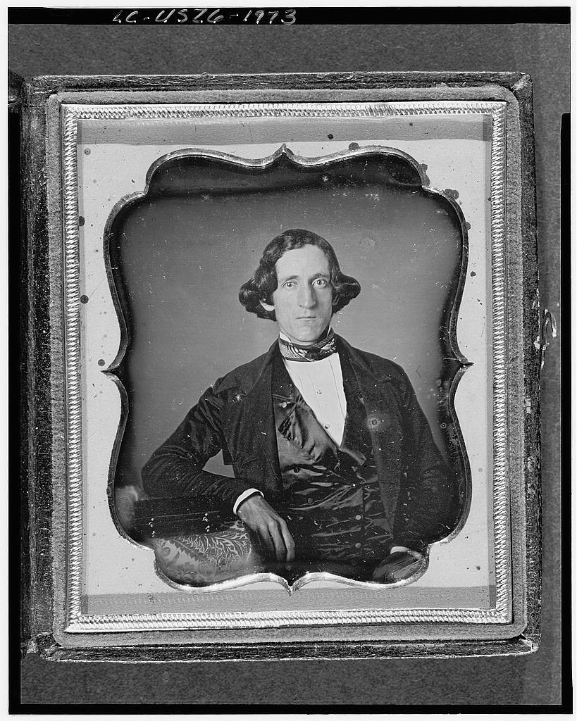 [Unidentified man, possibly Chester Fitts of Charlton, three-quarter length portrait, full face, with arm resting on table with tablecloth; case on table]