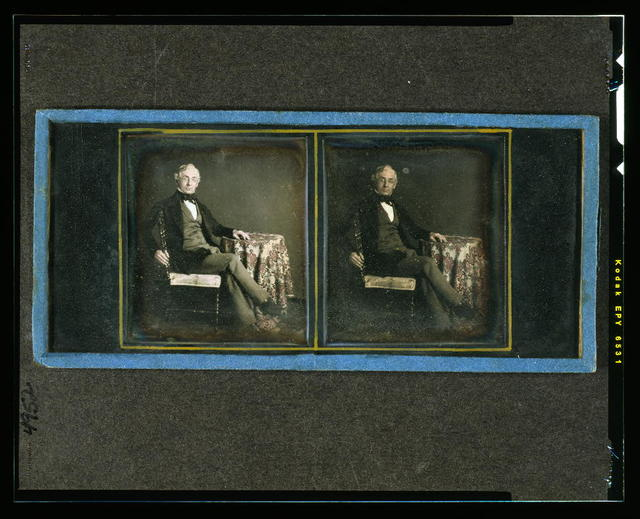 [William Y. McAllister, full-length, seated in chair with arm resting on table with tablecloth]