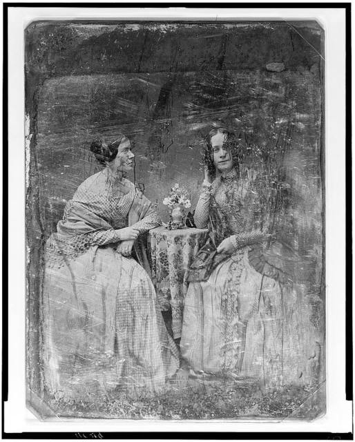 [Two unidentified women, full-length portraits, seated at table with tablecloth and bouquet]
