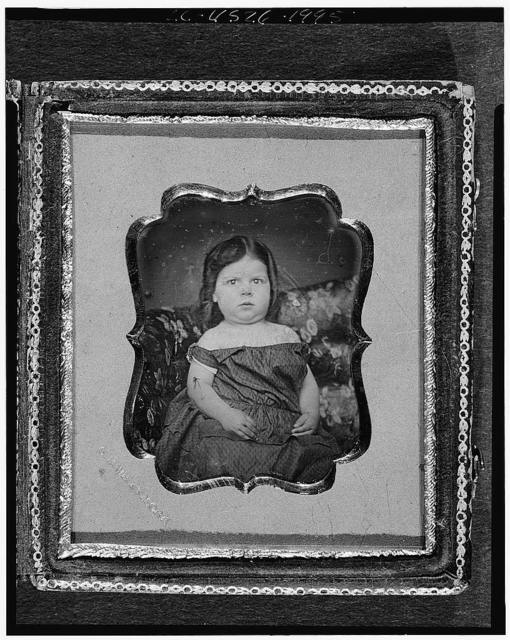 [Adeline Tapley Fuller Stowell, as a girl, three-quarters length portrait, facing front, seated on upholstered sofa]