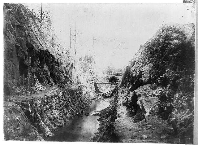 [Ditch with water leading to tunnel, with one man]