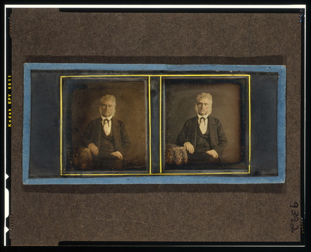 [John McAllister, three-quarter length portrait, seated, facing front with arm resting on table with tablecloth]