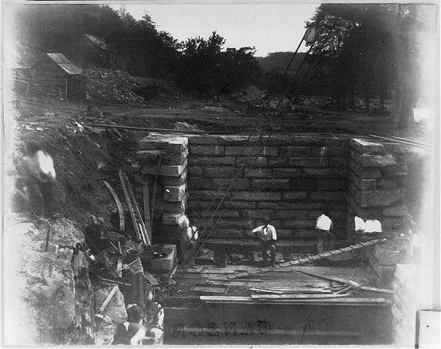 [Men working in deep pit with stone wall]