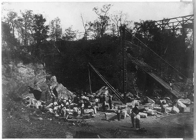 [Men working with large stone blocks]