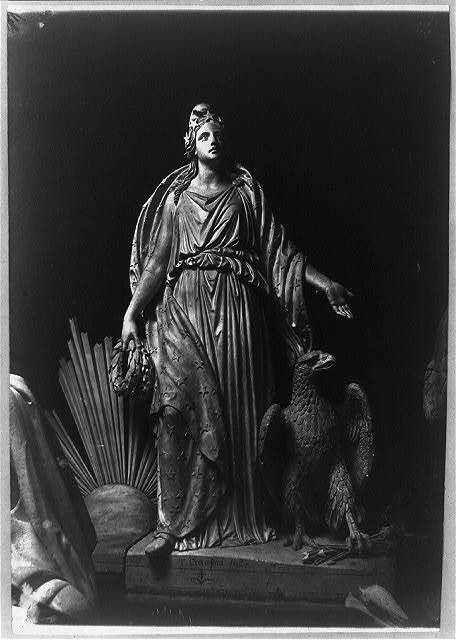 [Sculpture of female figure draped in robe; eagle beside her, clutching arrows in one of its claws. Signature of J. Crawford on base]