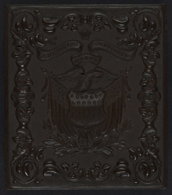 "[Union case for daguerreotype, ambrotype, or tintype showing eagle perched above shield with American flags with a banner stating ""The Union and Consitution"" above and a scroll frame]"