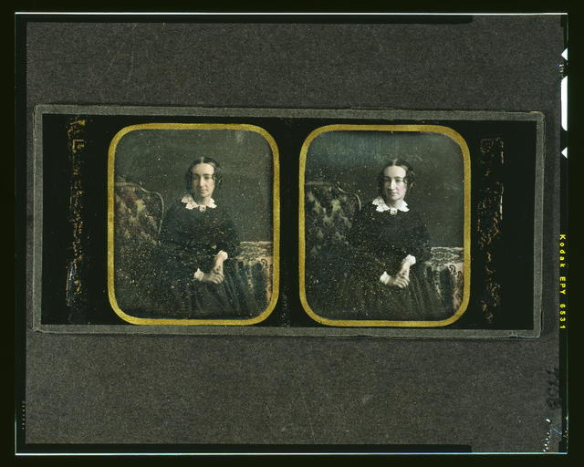 [Agnes Y. McAllister, three-quarters length, seated in ornate chair, with arm resting on table with tablecloth]