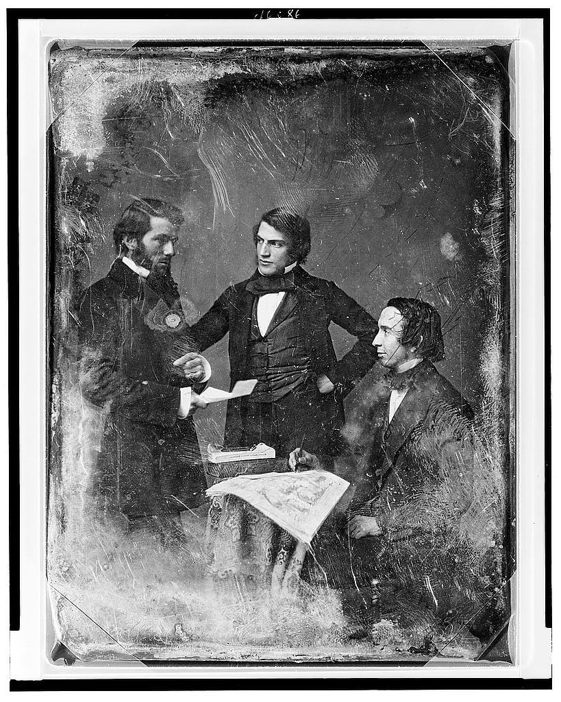 [Three unidentified men, all nearly full figures: man on left with side whiskers, standing, turned to the right, holding a piece of paper; center figure, standing, three-quarters to the left, one hand on hip; man on right, seated, in profile to the right, holding a pencil over a large print which, with two books, lies on a small table with tablecloth]