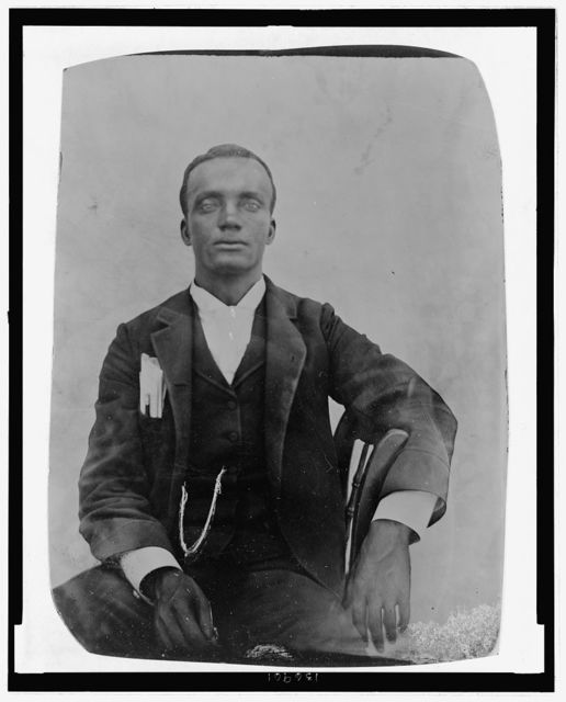 [Unidentified Liberian man in suit with watch fob and papers and pencil in his breast pocket]