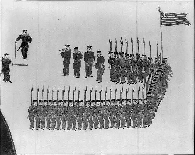 [U.S. Marines, led by four musicians, marching in formation toward two officers]
