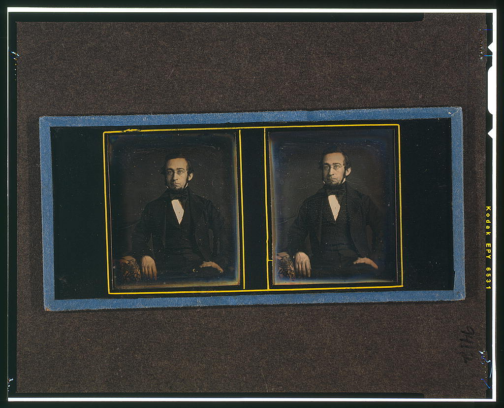 [Unidentified man, three-quarters length, seated, with arm resting on table with tablecloth]