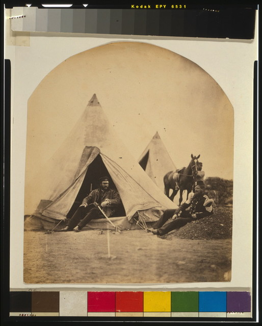 [Officer of the 57th Regiment sitting with a sword across his lap at opening to his tent, another officer sitting outside the tent, and a servant stands with a horse in the background]